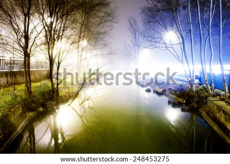 Cityscape at foggy night with trees and lamppost - stock photo