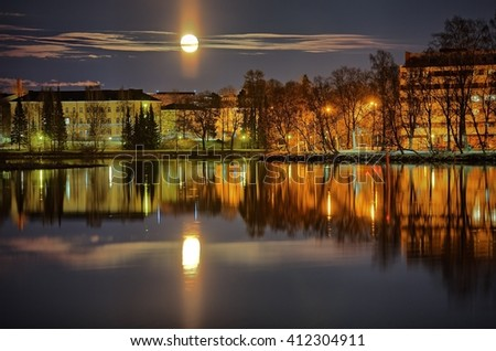 Cityscape in Finland at moonlit night. Reflections of citylights on the still water of the lake and the moon on the sky.