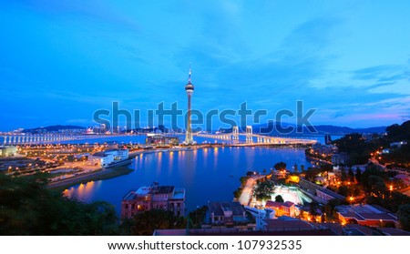 Cityscape in night with famous travel tower near river in Macao, China.