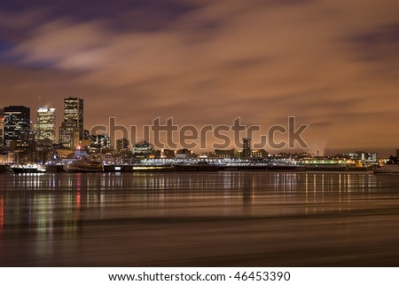 cityscape night scene Montreal Canada over river Saint Lawrence impressive and vibrant dusk sky color skyscrapers lights - stock photo