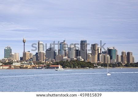 Cityscape of capital city Sydney across Harbour waters above Royal Botanic garden on a bright summer day.