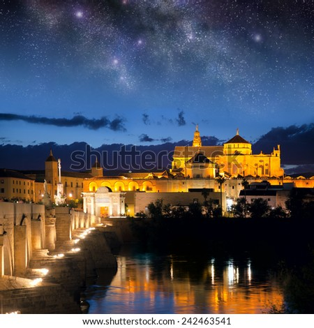 Cityscape of Cordoba at night with Roman bridge and Mezquita, Andalusia, Spain - sky with stars - stock photo