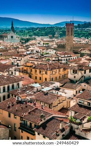 Cityscape of Florence on sunny day with multiple tiled roofs and historical monuments. Basilica di Santa Croce and Palazzo Vecchio are visible in distance. - stock photo