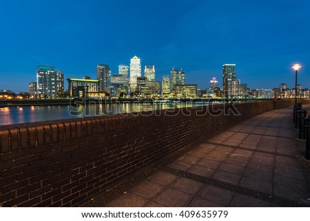 Cityscape of illuminated landmark Canary Wharf, London financial sky scrapers at blue hour