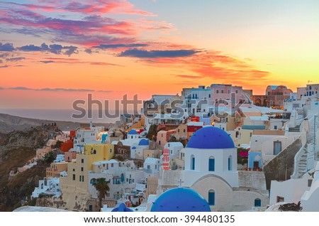cityscape of Oia, traditional greek village of Santorini,  with blue domes of churches at sunset, Greece, toned - stock photo
