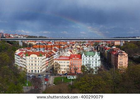 Cityscape of Prague, aerial view of prague taken from vysehrad castle complex captures detail of typical red rooftops  under Nusle Bridge and rainbow - stock photo