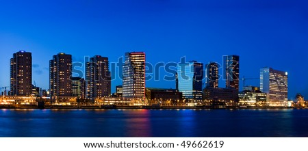 Cityscape of Rotterdam at dusk. Evening time. Buildings and Maas river