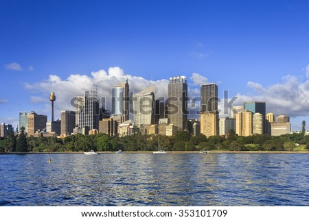 Cityscape of Sydney skyscraper towers and office buildings above Royal Botanic gardens reflecting in harbour waters on a sunny summer day - stock photo