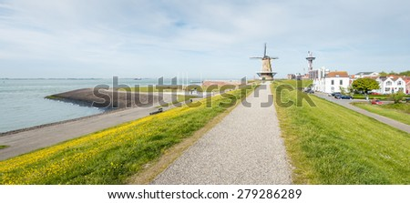 Cityscape of the Dutch city of Vlissingen from the seawall. The mill (Oranjemolen) at the end of the path is a flour mill built in 1691 or earlier and restored later. - stock photo