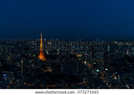 Cityscape of Tokyo at night, as seen from the top of one of the highest buildings in Roppongi Hills, with the illuminated Tokyo Tower glowing in the dark. Long exposure. - stock photo