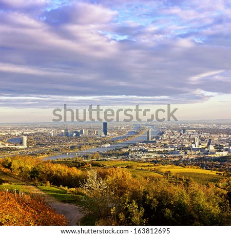 Cityscape of Vienna and Danube in the autumn at dusk. Right of river Danube the Millenium Tower, left the Danube City with its new DC Tower. Airport Vienna with its white Control Tower in the back. - stock photo