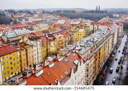 Cityscape of vintage residential district with bright colorful walls and tiled roofs near Vysehrad in Prague, Czech republic. Urban background in cloudy and rainy day. - stock photo