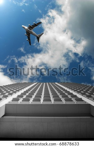 Cityscape photo of a modern office building with blue sky and airplane above