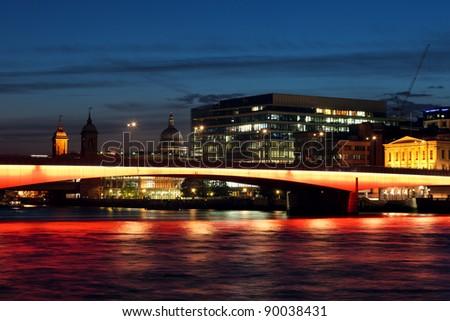Cityscape with illuminated London Bridge at night. - stock photo