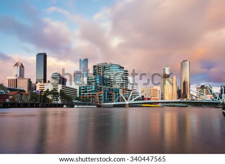 Cityspace of Dockland in Melbourne at sunset, long expsure, blurring clouds and smooth water - stock photo
