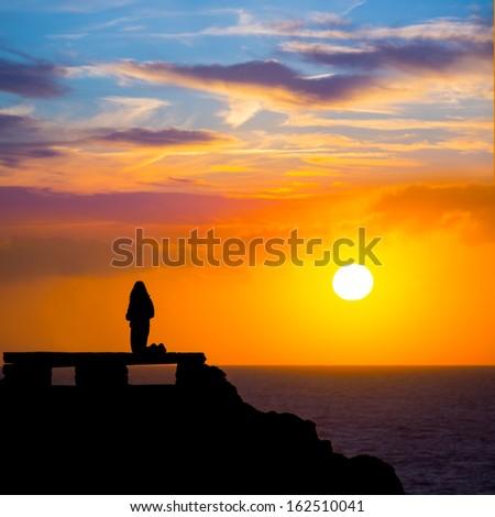 Ciutadella Menorca at Punta Nati orange sunset with girl backlight - stock photo