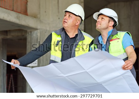Civil Engineer And Senior Foreman at construction site are inspecting ongoing production according to design drawings. - stock photo