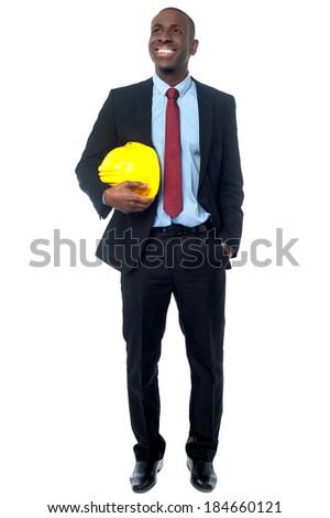Civil engineer holding yellow helmet and looking away - stock photo