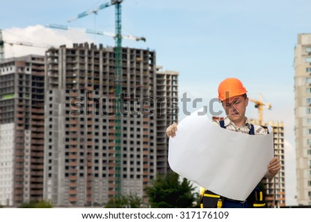 Civil engineer wearing a safety vest with a plan on construction site.