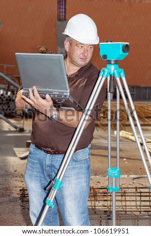 Civil engineer with leveling - stock photo
