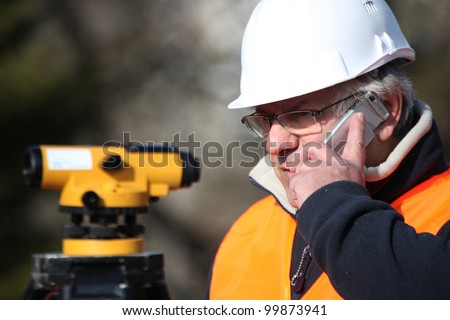 Civil engineer with surveying equipment - stock photo