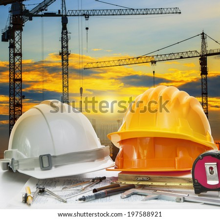 civil engineer working table with safety helmet and writing instrument against beautiful dusky sky and crane construction site - stock photo
