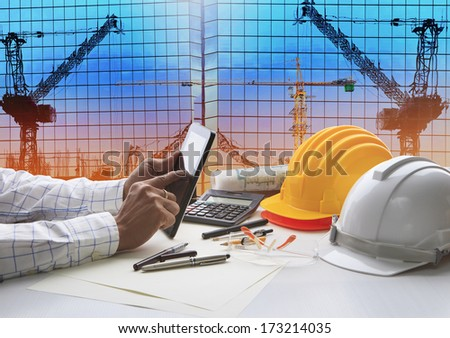 civil engineer working with tablet computer and construction plan on table top building crane construction background - stock photo