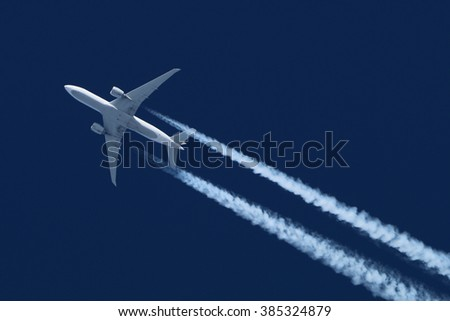 Civil wide-body airliner flying on a high altitude with condensation trail forming behind. - stock photo