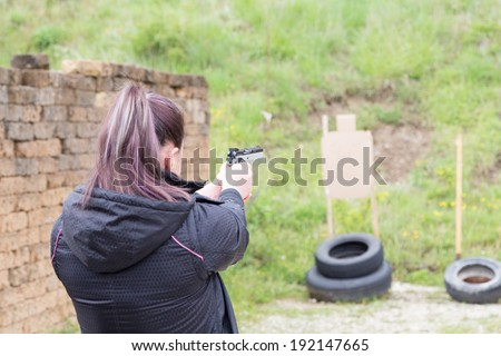 Civilian girl is practicing with her 9mm gun in a shooting range for improving her self-defense technique with gun - stock photo
