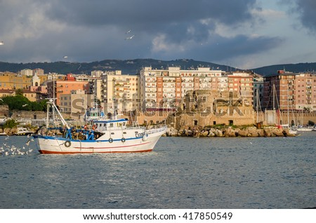 Civitavecchia, Italy - November 5, 2015: A view of Civitavecchia, also known as Port of Rome, from a pier of the harbour, showing an old fort, modern buildings and a fishing boat with many sea gulls.