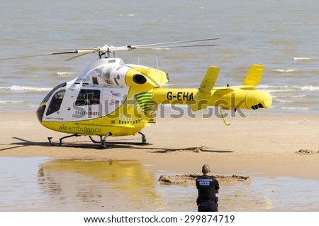 Clacton-on-sea, Essex, England, UK: 1 August 2013- Helicopter rescue, Yellow helicopter has landed on the beach to rescue someone in trouble. , who got into difficulty in the sea. - stock photo