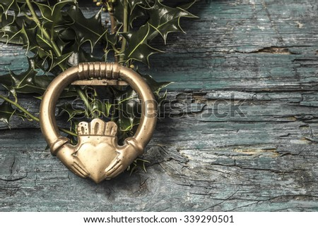 Claddagh and holly branches  irish symbol of love, friendship and loyalty in old wooden background - stock photo