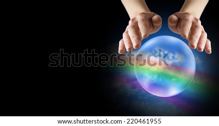Clairvoyant's hands hovering over crystal ball showing rainbow and blue sky on a black banner background - stock photo