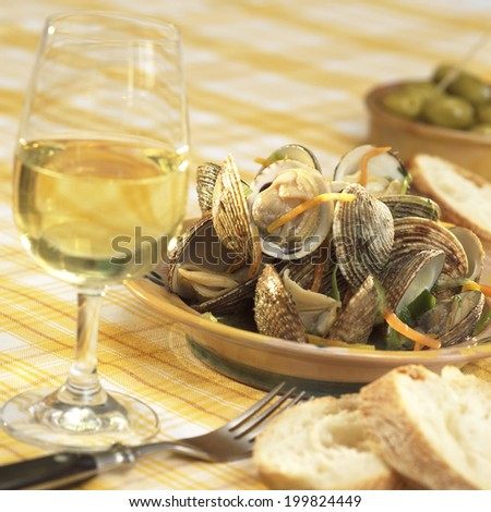 Clam shells in white-wine sauce and root vegetables served glass of white wine bread slices and olives - stock photo