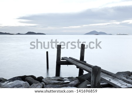 Clam sunset with jetty on sea - stock photo