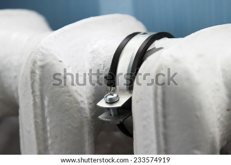 Clamp on the old white radiator - stock photo