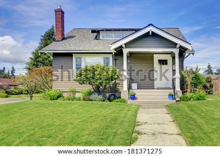 Clapboard siding house with tile roof and brick chimney. View of white column porch and green lawn