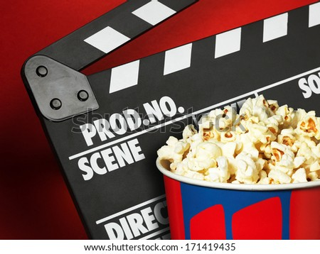 Clapper board and popcorn box on red background - stock photo
