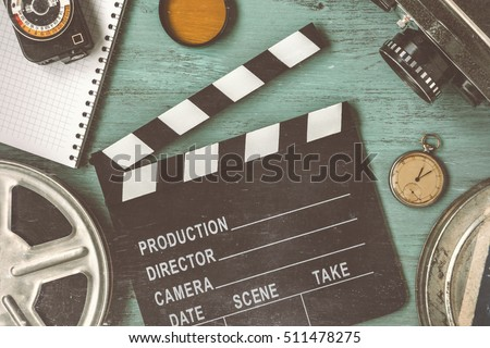 Clapperboard and a film reel, a stop watch, a notebook and a lens on the table