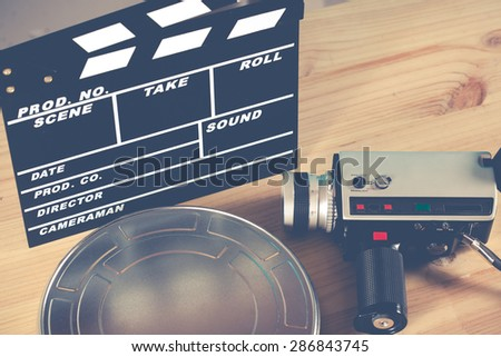 Clapperboard with his camera and tape virgin - stock photo