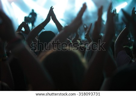 clapping crowd at the concert, rear view - stock photo