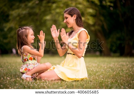 Clapping hands - mother playing with her daughter outdoor in nature - stock photo
