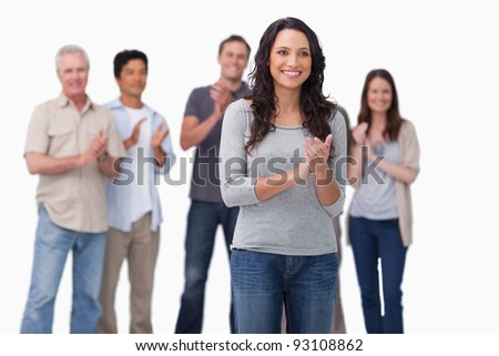 Clapping young woman with friends behind her against a white background - stock photo
