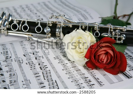 Clarinet with red and white rose on sheet music - stock photo