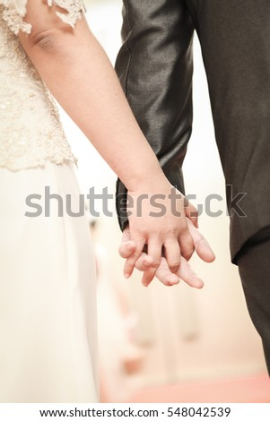 Clasping hands of Bride and Groom in wedding ceremony
