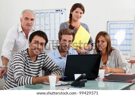 Class and teacher gatherd around laptop - stock photo