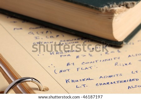 Class notes for graduate class in general relativity on yellow paper in ring binder with old damaged book - stock photo