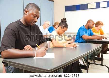 Class of adult college students taking a test.  Focus on guy in front left. - stock photo