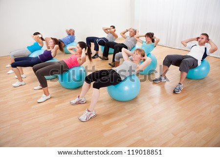 Class of diverse people doing pilates exercises in a gym doing head lifts to strengthen their abdominal muscles