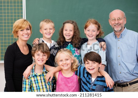 Class of happy smiling young students posing with their teachers, an attractive young woman and older man, in front of the class blackboard